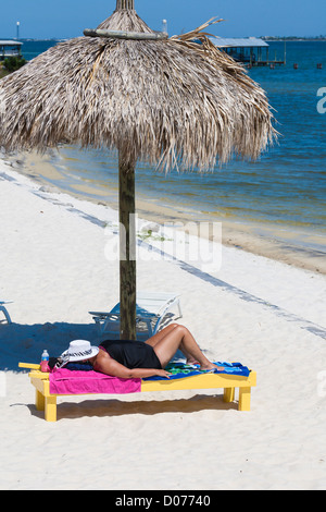 Overweight senior woman lies on lounge chair under umbrella while sunbathing at Navarre, Florida - Stock Photo