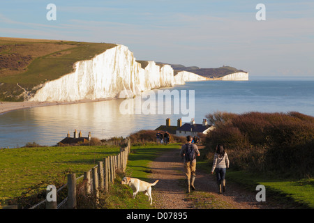 Walkers on the South Downs Way with Seven Sisters cliffs and coastline viewed from Seaford Head East Sussex England - Stock Photo