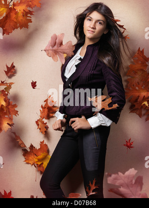 Teenage girl in fashionable clothes and red falling autumn leaves beautiful artistic fall fashion photo - Stock Photo