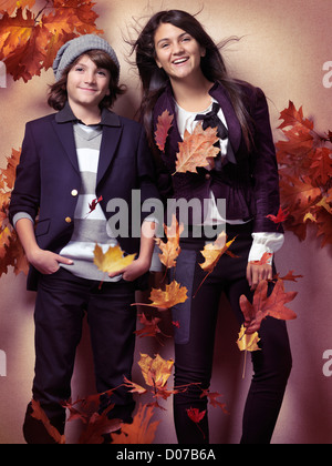Smiling boy and a teenage girl in fashionable clothes and red falling autumn leaves beautiful artistic fall fashion - Stock Photo