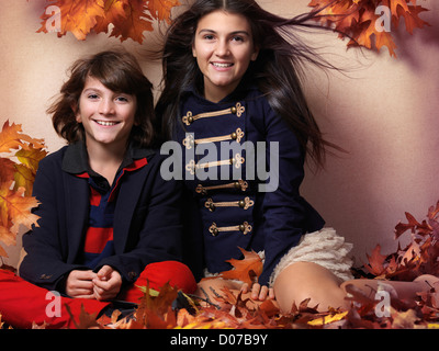 Smiling boy and a teenage girl in trendy clothes sitting together surrounded with red autumn leaves beautiful fall - Stock Photo