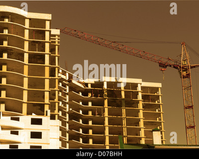 Construction of new residential buildings by pouring concrete (gold tone) - Stock Photo