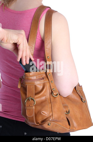 Pickpocketing a mobile out of a handbag of a woman - Stock Photo