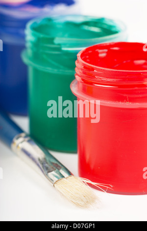 Closeup view red, green and blue cans with gouache - Stock Photo