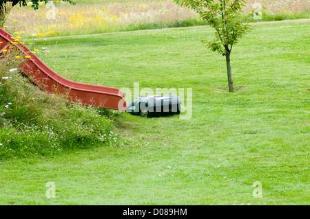 husqvarna robotic robot mower mowers grass cutter cutting the garden hi tech - Stock Photo