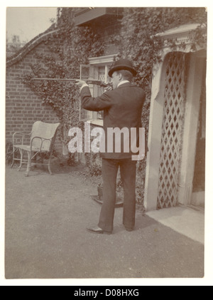 Edwardian man outside his house with an air rifle, looking as if he is defending his property. sportsman, sportsmen, - Stock Photo