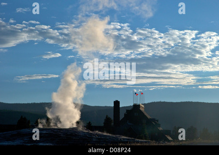 Old Faithful Geyser erupting in summer evening light, with Old Faithful Inn behind, Yellowstone National Park, Wyoming, - Stock Photo