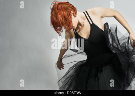 Beautiful ballerina wearing black tutu dancing over textured gray background - Stock Photo