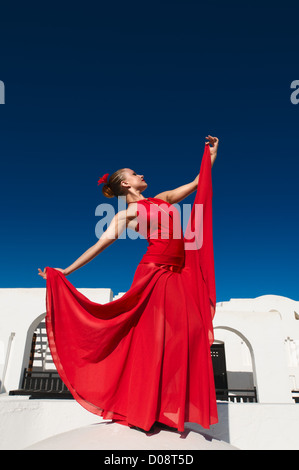 Attractive flamenco dancer wearing traditional red dress with flower in her hair - Stock Photo