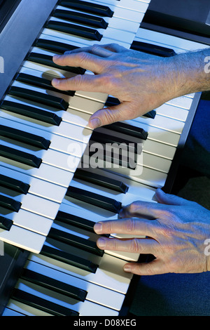 Playing a two manual electric organ. - Stock Photo