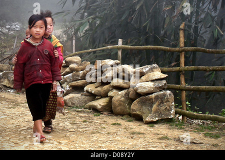CHILDREN COMING HOME FROM SCHOOL IN THE MOUNTAINS NEAR SAPA VIETNAM ASIA - Stock Photo