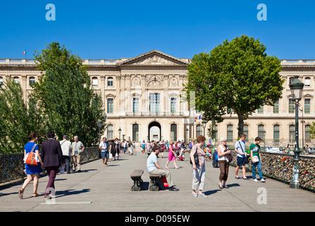 People walking across the Pont des Arts a pedestrian bridge across the River Seine facing the Louvre museum Paris - Stock Photo