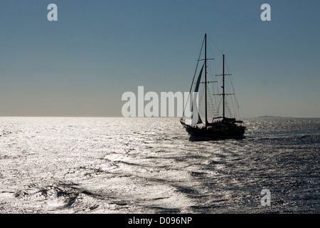 Greek tourist sailing boat silhouetted on silvery sea returning to Kos from nearby Greek Islands - Stock Photo