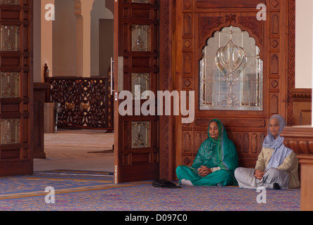Two elderly Indian Asian Sikhs Sat On The Floor In a Darbar Sahib Of A Sikh Gurdwara With Hands in Prayer - Stock Photo