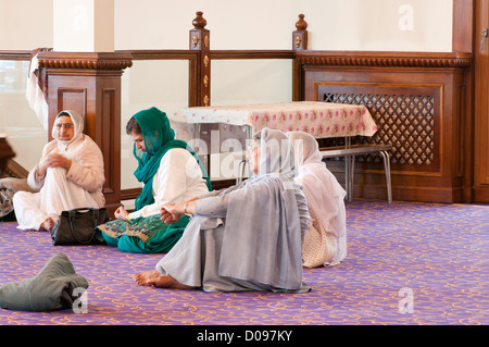 Female Indian Asian Sikhs Sat On The Floor In a Darbar Sahib Of A Sikh Gurdwara Indian Temple - Stock Photo