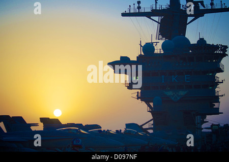 The Nimitz-class aircraft carrier USS Dwight D. Eisenhower (CVN 69) prepares for night operations as the sun sets. - Stock Photo