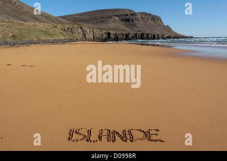 THE FRENCH NAME ICELAND WRITTEN IN EPHEMERAL MANNER IN SAND BEACH RAUDISANDUR REGION WESTERN FJORDS VESTFJORDS ICELAND - Stock Photo