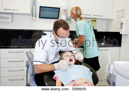 A male dentist examining a young girls teeth, dental nurse in the background - Stock Photo