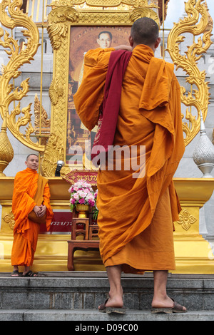 BUDDHIST MONK HAVING HIS PICTURE TAKEN IN FRONT PHOTO KING THAILAND RAMA IX ON STEPS WAT TRAIMIT TEMPLE OR TEMPLE - Stock Photo