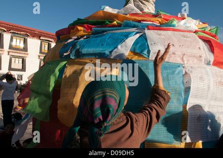 Prayer flags cover pagoda as pilgrims pray at Jokhang Temple on Barkhor Square at sunset, Lhasa, Tibet, China - Stock Photo
