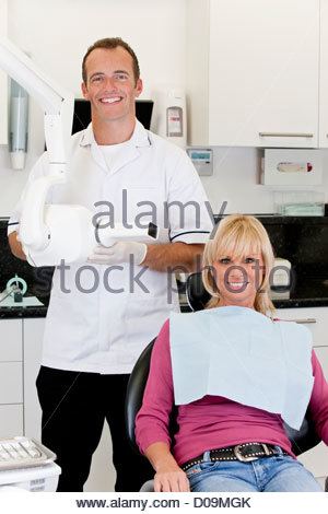 A male dentist with a female patient in his surgery - Stock Photo