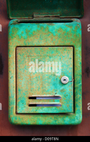 Old rusty mailbox on the shabby gate in Italy - Stock Photo