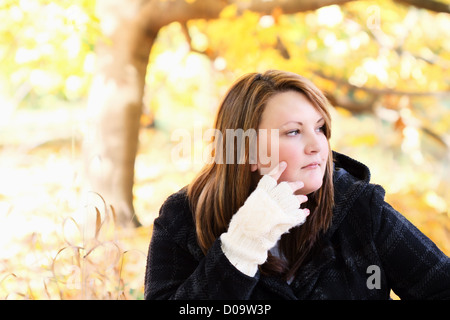 Beautiful young thoughtful woman sitting outdoors on a gorgeous autumn day. - Stock Photo