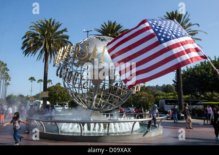 AMERICAN FLAG IN FRONT GLOBE HOLDING LOGO FOR MOVIE PRODUCTION COMPANY UNIVERSAL STUDIOS LOS ANGELES CALIFORNIA - Stock Photo