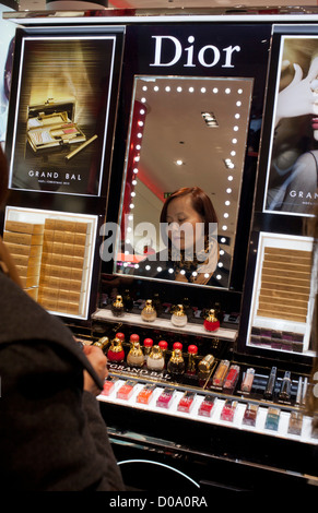 Chinese tourist trying Dior products in a shopping mall in Paris, France - Stock Photo