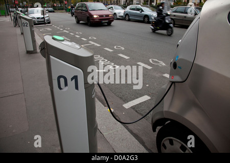 Electric car being charged in the streets of Paris, France - Stock Photo