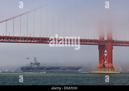 Aircraft carrier USS Carl Vinson passes slowly under the Golden Gate Bridge during Fleet Week as helicopter hovers - Stock Photo