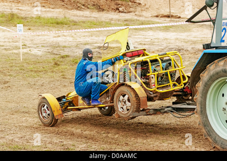 The tractor tows on parking broken racing buggy. Episode 4. - Stock Photo