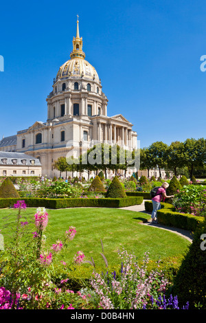 Person looking at the flowers in the gardens of the Eglise du Dome Les Invalides napoleons tomb Paris France EU - Stock Photo