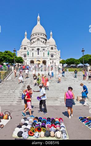 Men selling souvenirs to Crowds of tourists on the steps below Sacre Coeur  Paris France EU Europe - Stock Photo
