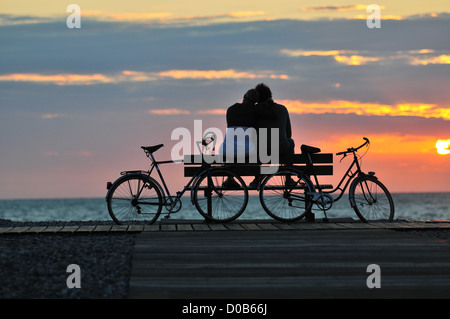 COUPLE SITTING ON A BENCH AT SUNSET CAYEUX-SUR-MER BAY OF SOMME SOMME (80) FRANCE - Stock Photo