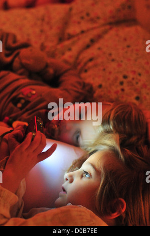LITTLE GIRLS IN BED IN THE EVENING LOOKING AT PHOTOS ON THEIR DIGITAL CAMERA SOMME (80) FRANCE - Stock Photo