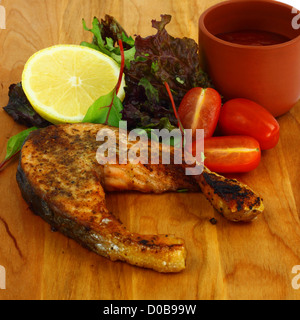 Salmon roasted steak served on the wooden board with lemon, lettuce, tomatoes and red sauce - Stock Photo