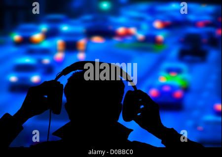 policeman monitoring heavy night road traffic from bridge - Stock Photo