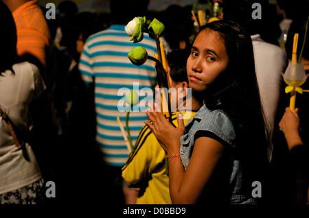young Thai woman prays w/ candle, incense & Lotus flowers, Wat Saket, Phu Khao Thong (Golden Mountain), Bangkok, - Stock Photo