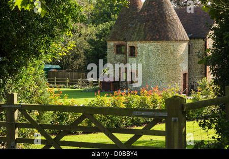 A beautiful oast house and garden on a sunny day. - Stock Photo