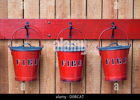 Three fire buckets hung on a wooden fence SS Great Britain Dockyard Museum, Bristol, England, UK