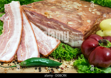 Still life with sliced romanian bacon and vegetables - Stock Photo