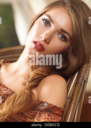 Soft romantic beauty portrait of a young beautiful woman with her hair in a braid sitting in a wooden rocking chair - Stock Photo