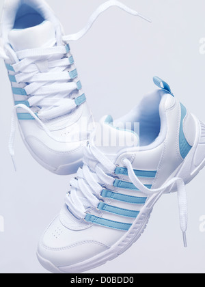 White sneakers, running shoes in mid air artistic still life isolated on white background - Stock Photo