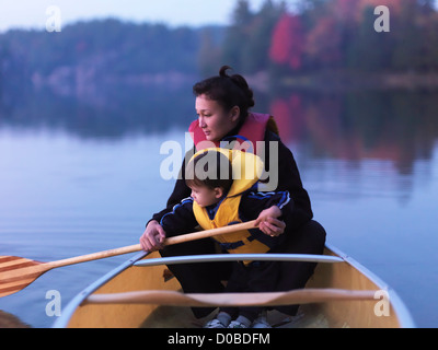Mother with a three year old boy learning to paddle a canoe, fall nature scenery. Kilarney, Ontario, Canada. - Stock Photo