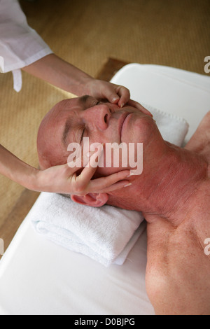 Senior man receiving head-massage - Stock Photo