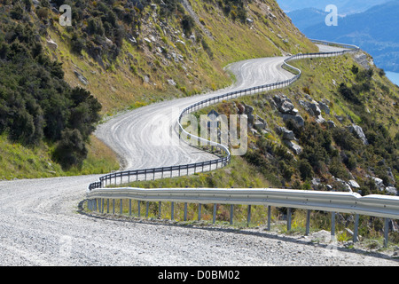 Gravel road winds along a steep mountainside in The Remarkables, near Queenstown. - Stock Photo