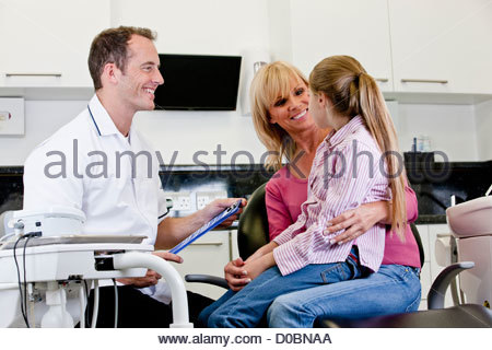 A male dentist talking to a young girl patient and her mother - Stock Photo