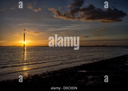 sunset on the solent looking across Southampton Water to Fawley Power Station - Stock Photo