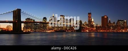 Panorama skyline New York City dusk as seen Brooklyn side looking across East River Brooklyn Bridge towers Lower - Stock Photo
